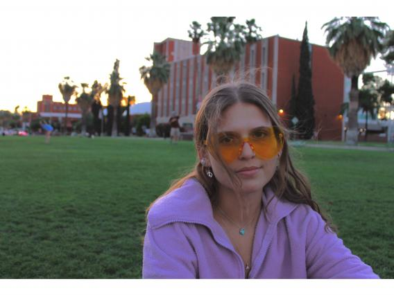 A headshot of Emerson posing outside on campus lawn wearing yellow sunglasses and a pink hoodie